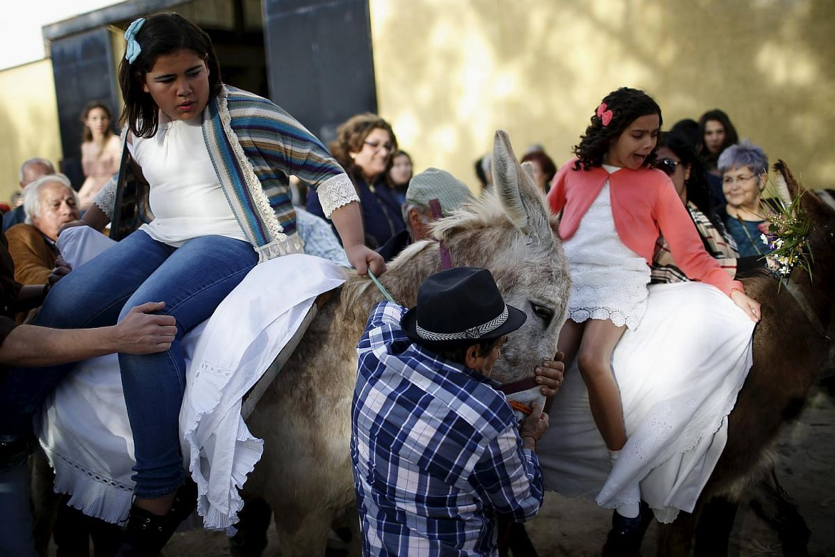 "Two girls sitting on donkeys before joining in the ""Virgem da Atalaia"" procession during Holy Week at Alcochete, near Lisbon, Portugal on March 27, 2016."