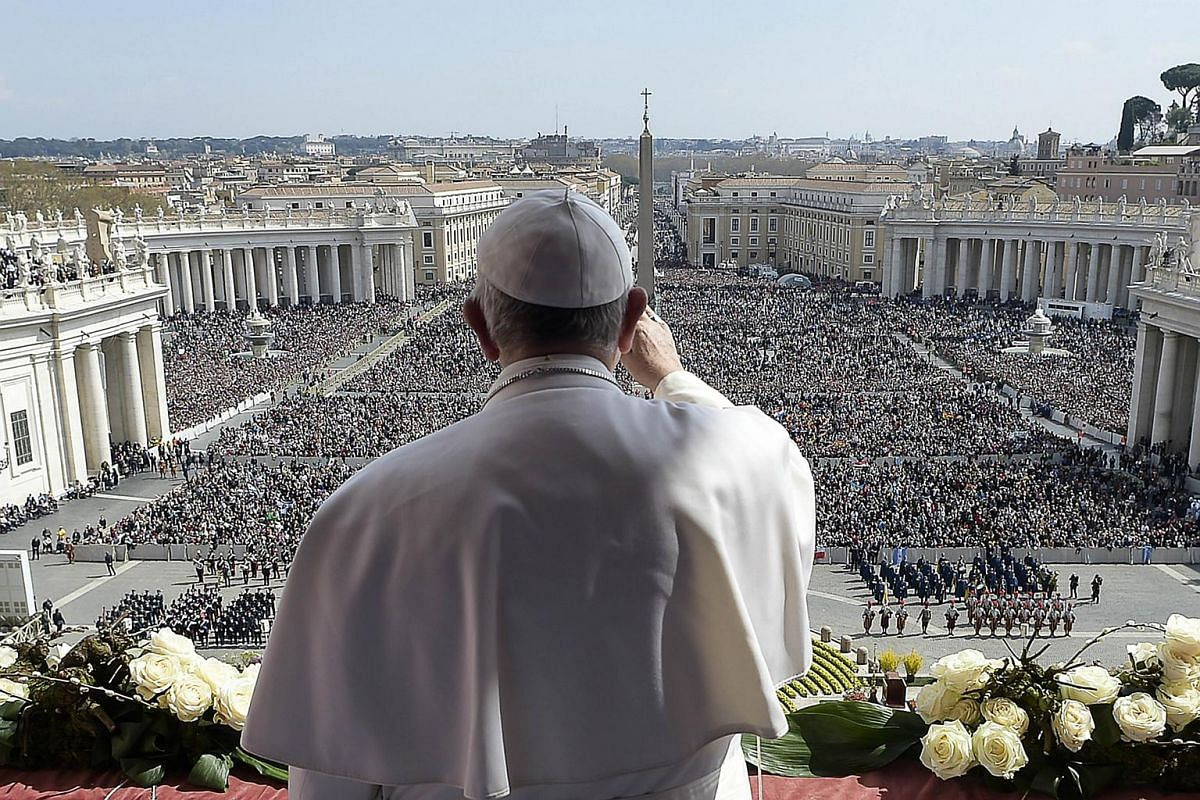"This handout picture released by the Vatican press office shows Pope Francis waving to the crowd from the central loggia of St Peters' basilica during the ""Urbi et Orbi"" blessing for Rome and the world following the Easter Sunday mass on March 27, 20"