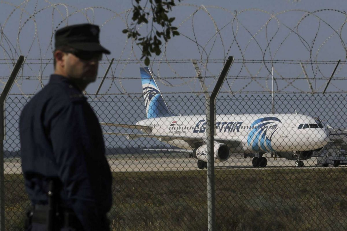 A policeman stands guard at Larnaca Airport near a hijacked EgyptAir A320 plane on March 29, 2016.