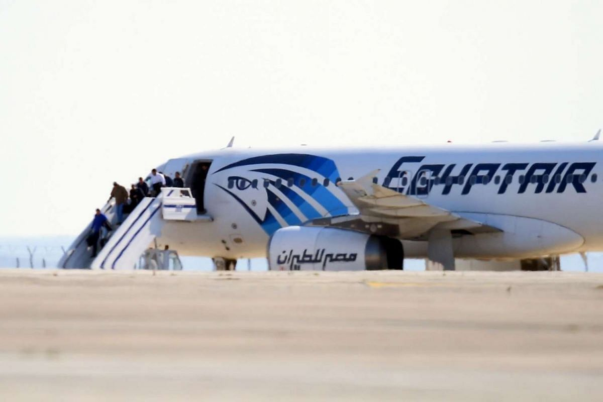 Passengers disembark an EgyptAir Airbus A320 sitting on the tarmac of Larnaca aiport after it was hijacked and diverted to Cyprus on March 29, 2016.