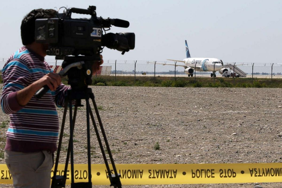A cameraman takes footage of the hijacked EgyptAir A320 plane parked at a sealed-off area of the Larnaca Airport, in Larnaca, Cyprus on March 29, 2016.