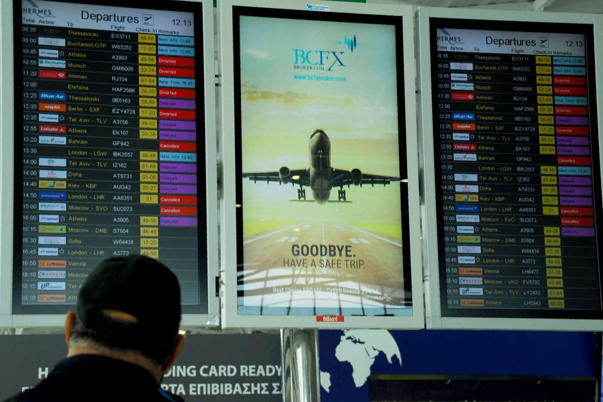 A stranded passenger checks the screens at the departure lounge of Larnaca airport on March 29, 2016.