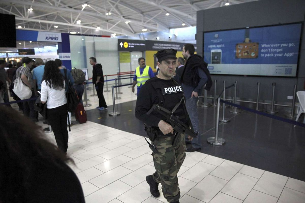 A policeman patrols in the departure hall of Larnaca Airport in Larnaca, Cyprus, March 29, 2016.