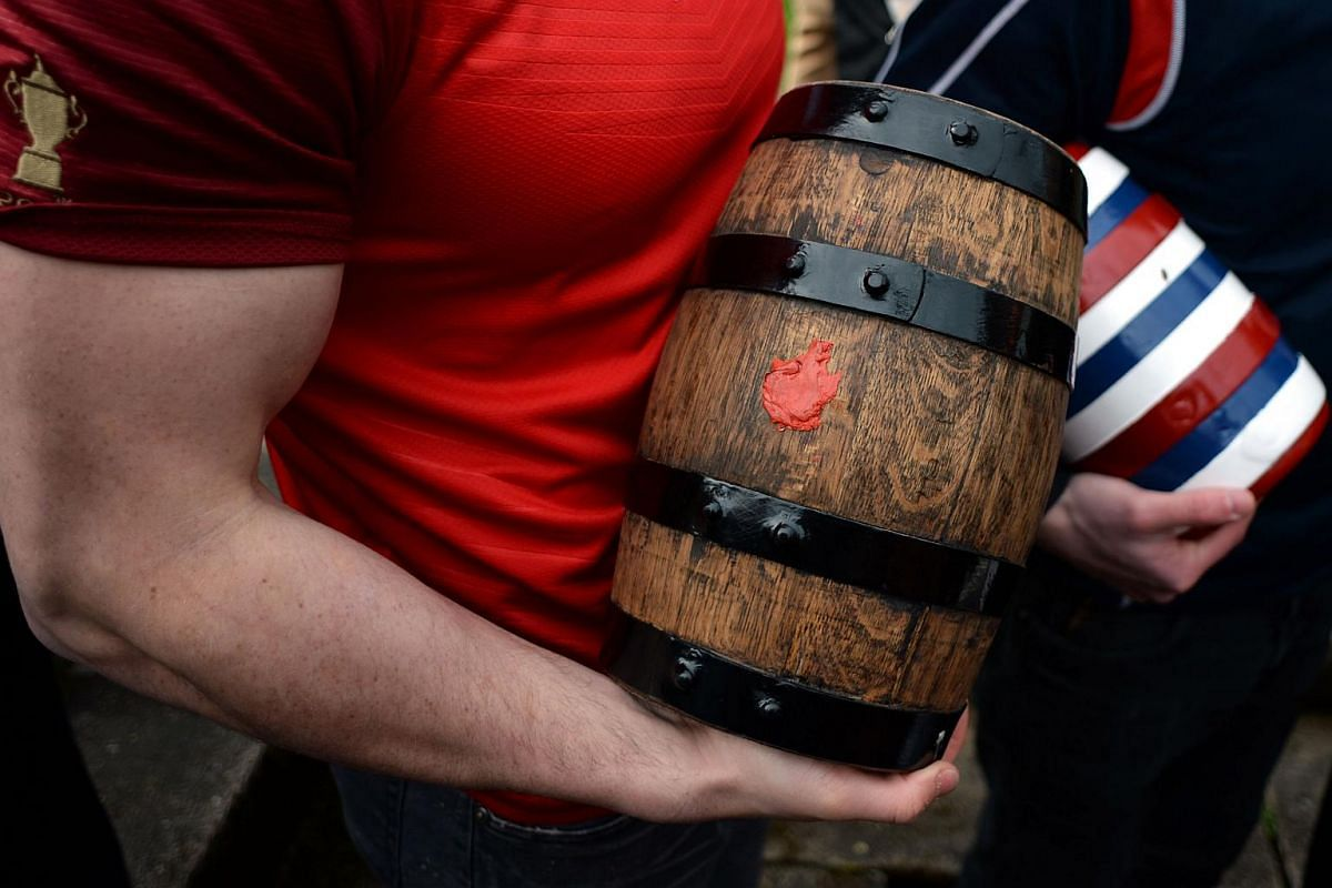Men hold kegs of ale for the Bottle Kicking Match, which are adorned with ribbons, near the village of Hallaton, on March 28, 2016.