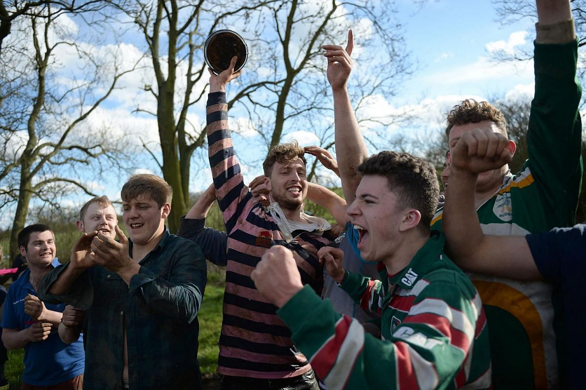 Members of the Medbourne team celebrate their goal in the Bottle Kicking Match,  near the village of Hallaton, on March 28, 2016.