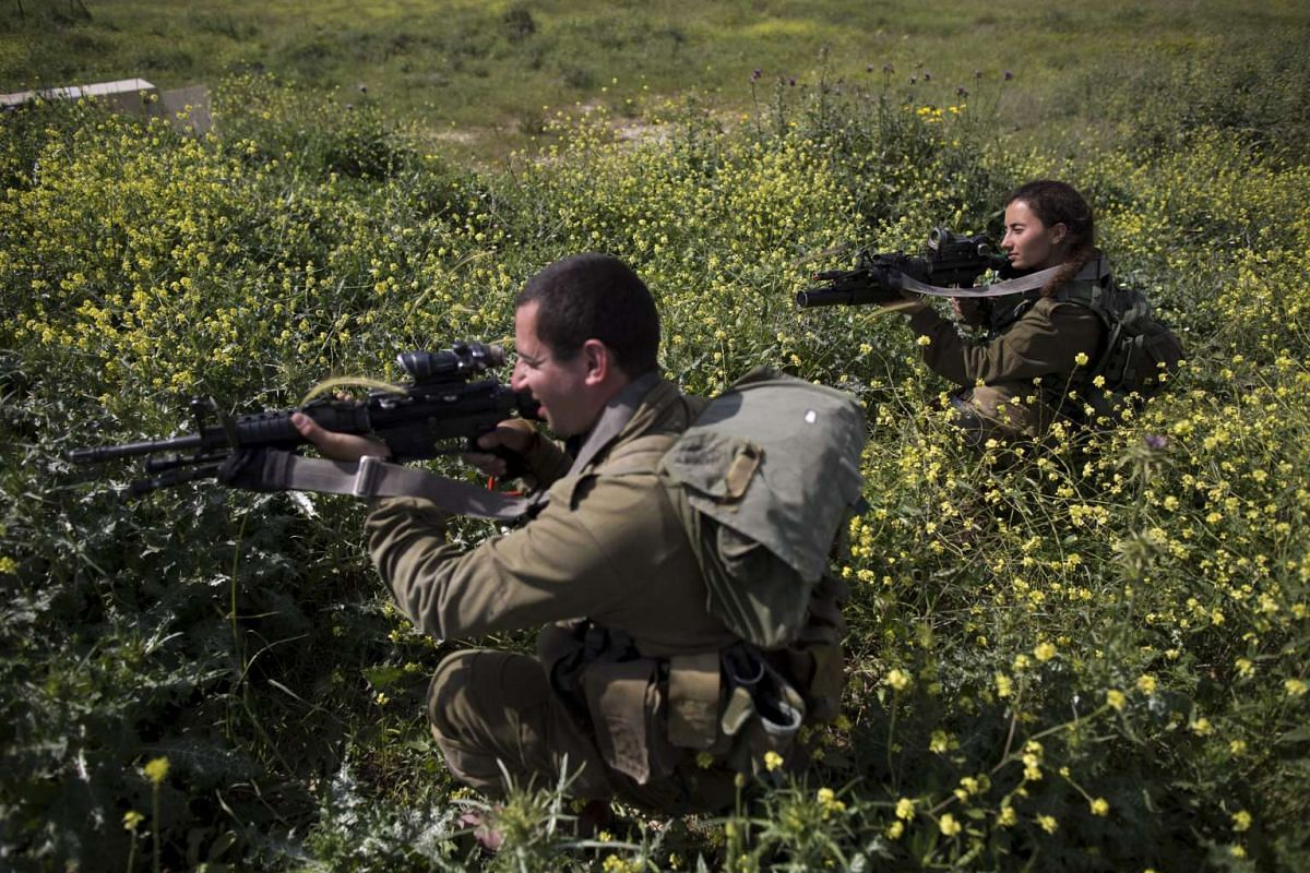 Israeli soldiers from the new mixed-sex army battalion called Bardelas (Cheetah) during an urban warfare exercise near Regavim northen Israel, on March 29, 2016.