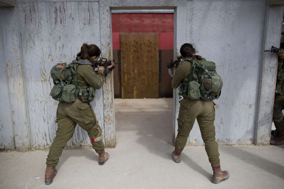 Israeli female soldiers from the new mixed-sex army battalion called Bardelas (Cheetah) during an urban warfare exercise near Regavim northen Israel, on March 29,  2016.