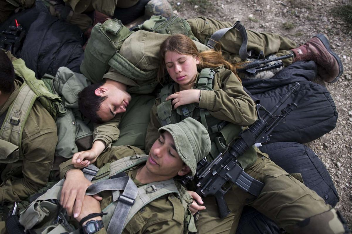 Israeli soldiers from the new mixed-sex army battalion called Bardelas (Cheetah) rest during an urban warfare exercise near Regavim northen Israel, on March 29, 2016.