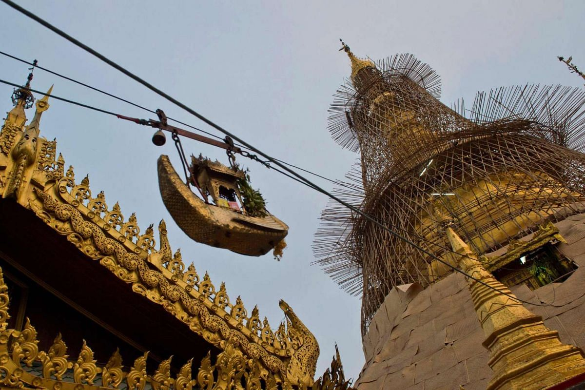 A vessel in the form of a boat delivering devotees offerings of gold leaf to the tower of Sule Pagoda on March 4.