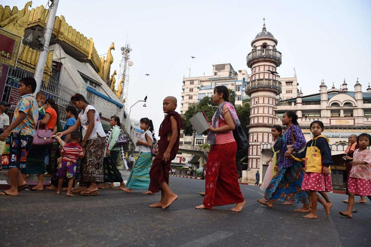 Devotees arriving at the gold-covered Sule Pagoda (left) on March 24.