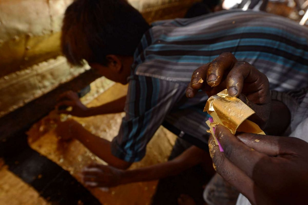 A craftsman preparing a square gold leaf to cover the Sule Pagoda's tower on March 8.
