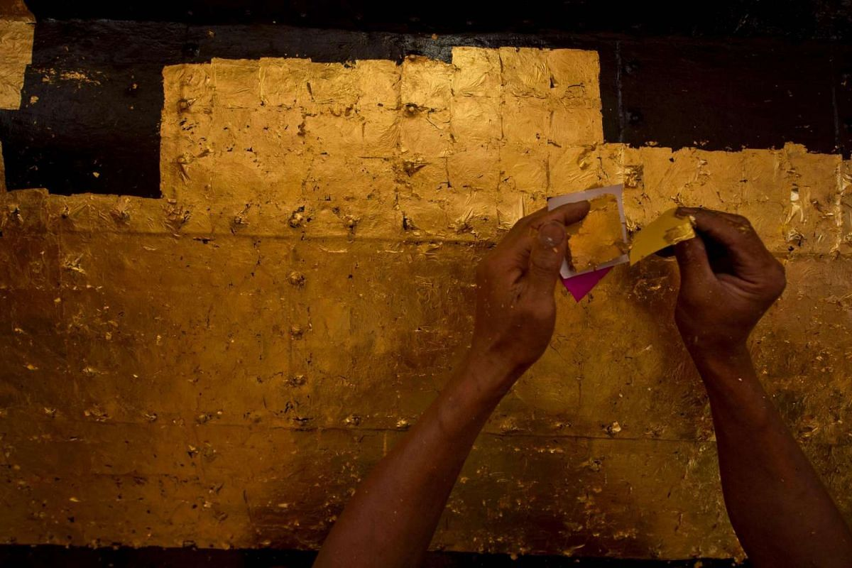 A craftsman using square gold leaf to cover a section of Sule Pagoda's tower during renovations on March 8.