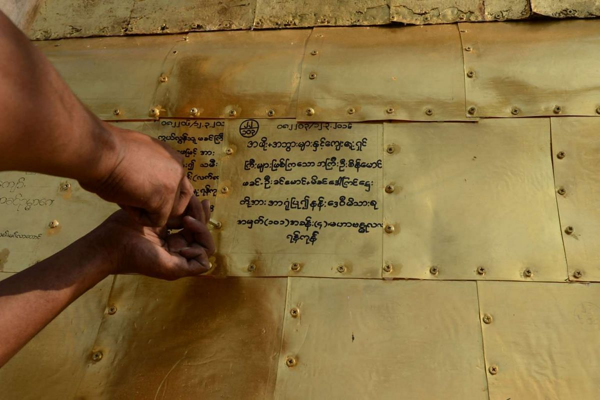 A craftsman attaching a pure gold plate with the inscription of a donor's name and dedication onto the Sule Pagoda's tower on March 12.