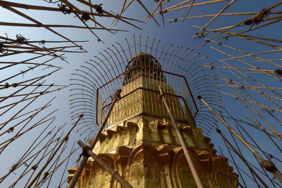 Bamboo scaffolding surrounding the Sule Pagoda tower, covered in gold and decorated with gemstones, on March 12.