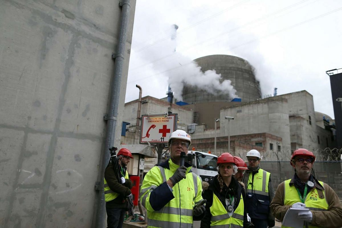 Director of the construction site of the third European generation Pressurised Water Reactor (EPR) Antoine Menager talks in front of one of the two nuclear reactors.