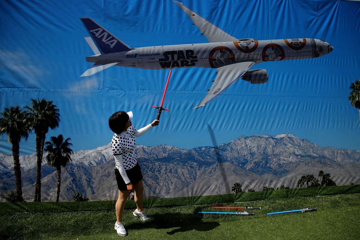 Japan's Shiho Oyama plays with a light saber toy during the Pro-Am as a preview for the 2016 ANA Inspiration Championship in California, on March 30, 2016.