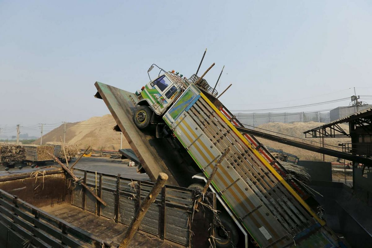 Trucks deliver the sugar cane harvest inside a sugar mill at Pakchong district, Thailand, on March 22, 2016.