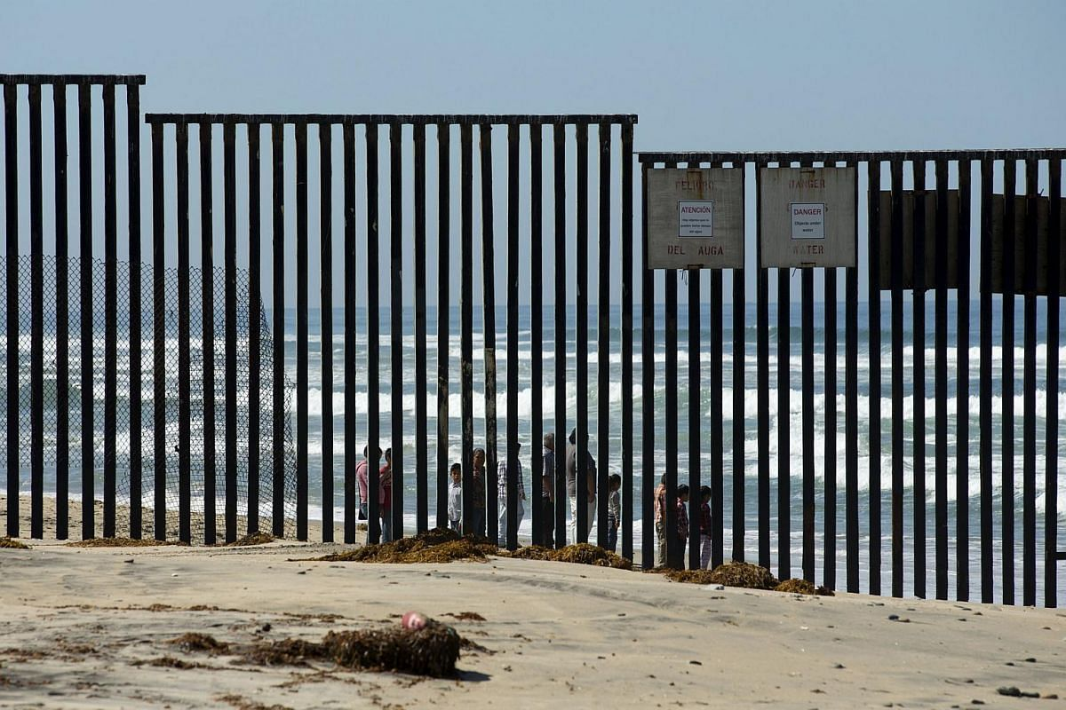 People standing on the Mexican side of the beach along the Pacific Ocean where a fence separates the United States from Tijuana, Mexico, near San Ysidro, California on March 31, 2016.