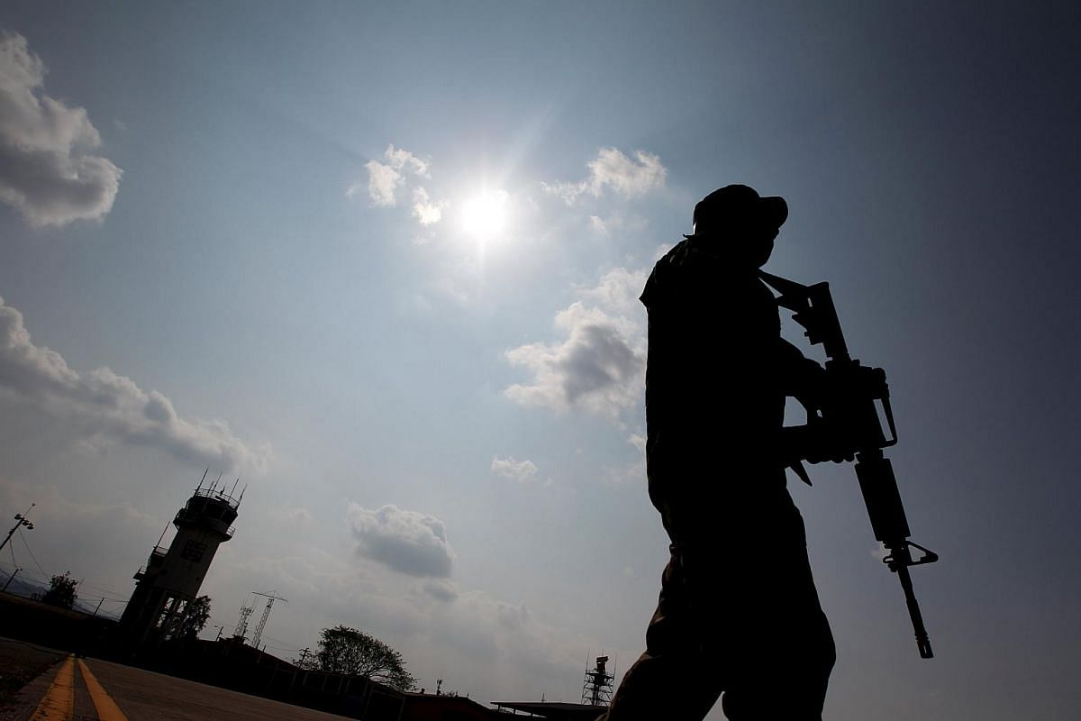 A soldier is silhouetted as he keeps watch before the arrival of Honduran President Juan Orlando Hernandez to a ceremony to announce the new international airport at Palmerola Air Base in Comayagua, Honduras, on March 31, 2016.