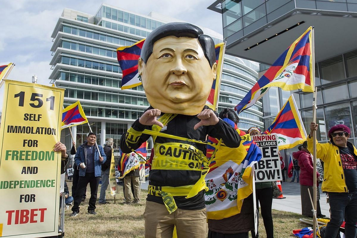 Tibetans protesting against China with a mask depicting President of China Xi Jinping, outside the security perimetre near the Walter E. Washington Convention Center during the Nuclear Security Summit in Washington, DC, on March 31, 2016.