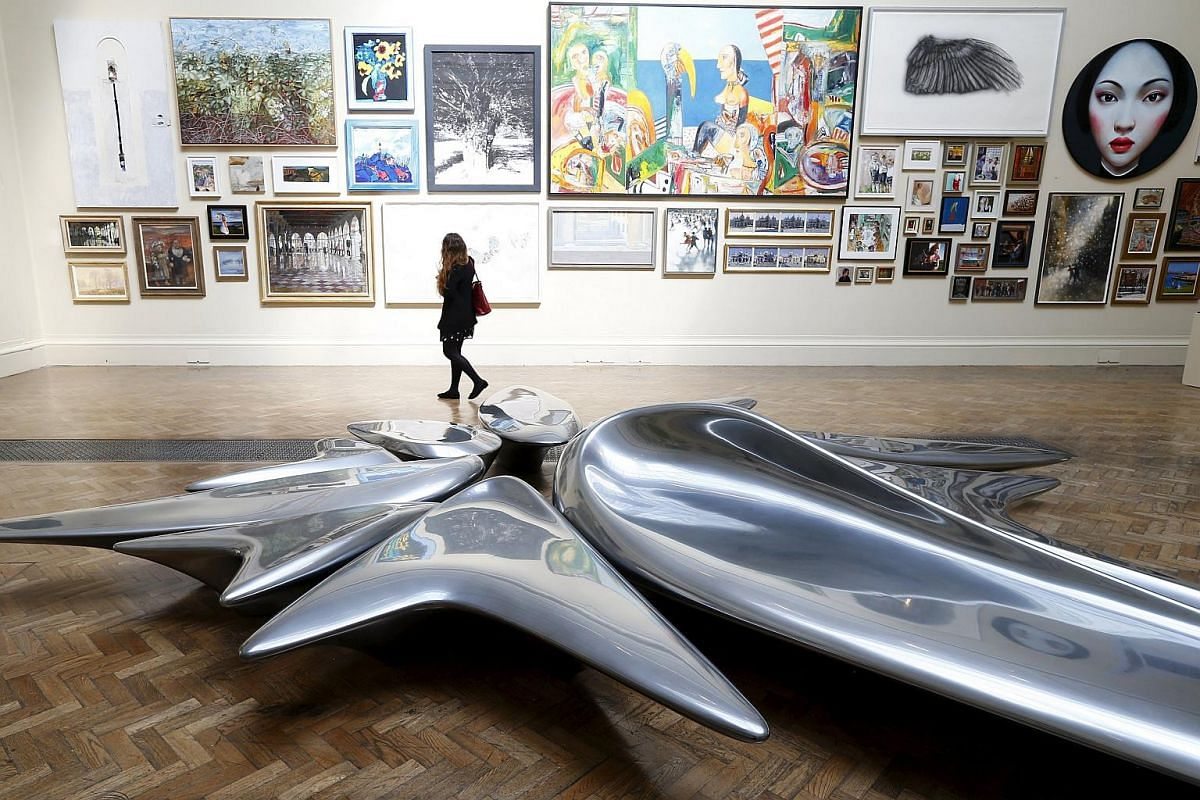 A woman looking at paintings behind a sculpture by Hadid, titled Kloris, at the Royal Academy of Arts in London, in 2013.