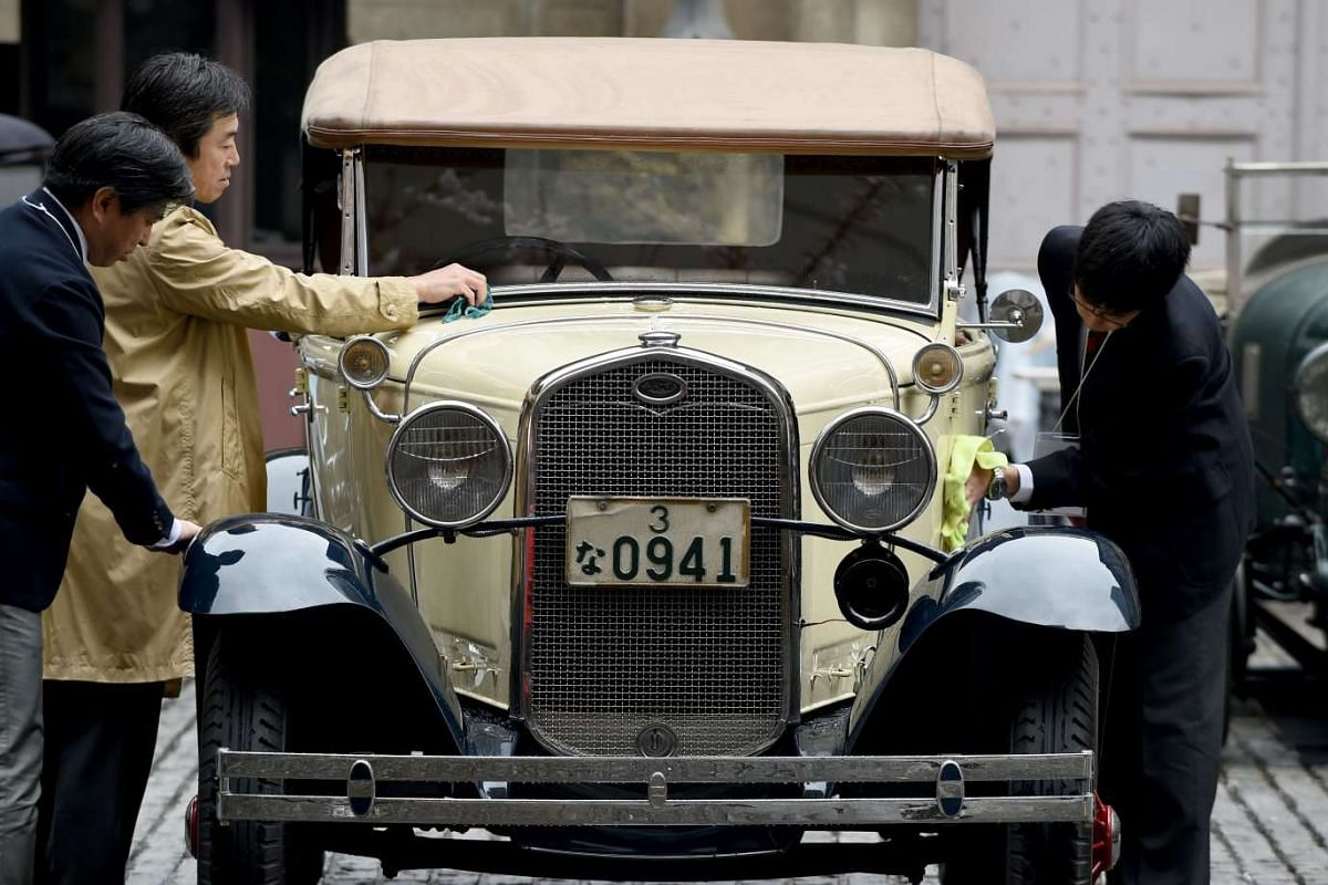 Owners wipe rain drops from their 1931 Ford Model A vintage car during the Japan Classic Automobile 2016 event in Tokyo on April 3, 2016.