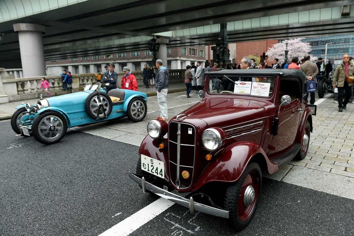 A 1937 Dutsun Roadstar (right), a 1928 Bugatti T37A and other vintage cars are on display on the Nihonbashi bridge during the Japan Classic Automobile 2016 event in Tokyo on April 3, 2016.