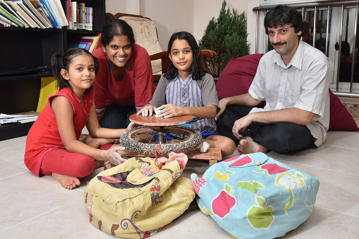 Dr Adrian Curic, Dr Kiruthika Ramanathan Curic and their daughters Anjali, nine, and Sophia, seven, with some of the things they have created from used materials, such as schoolbags from old pillow cases (foreground) and a pottery wheel from an old s