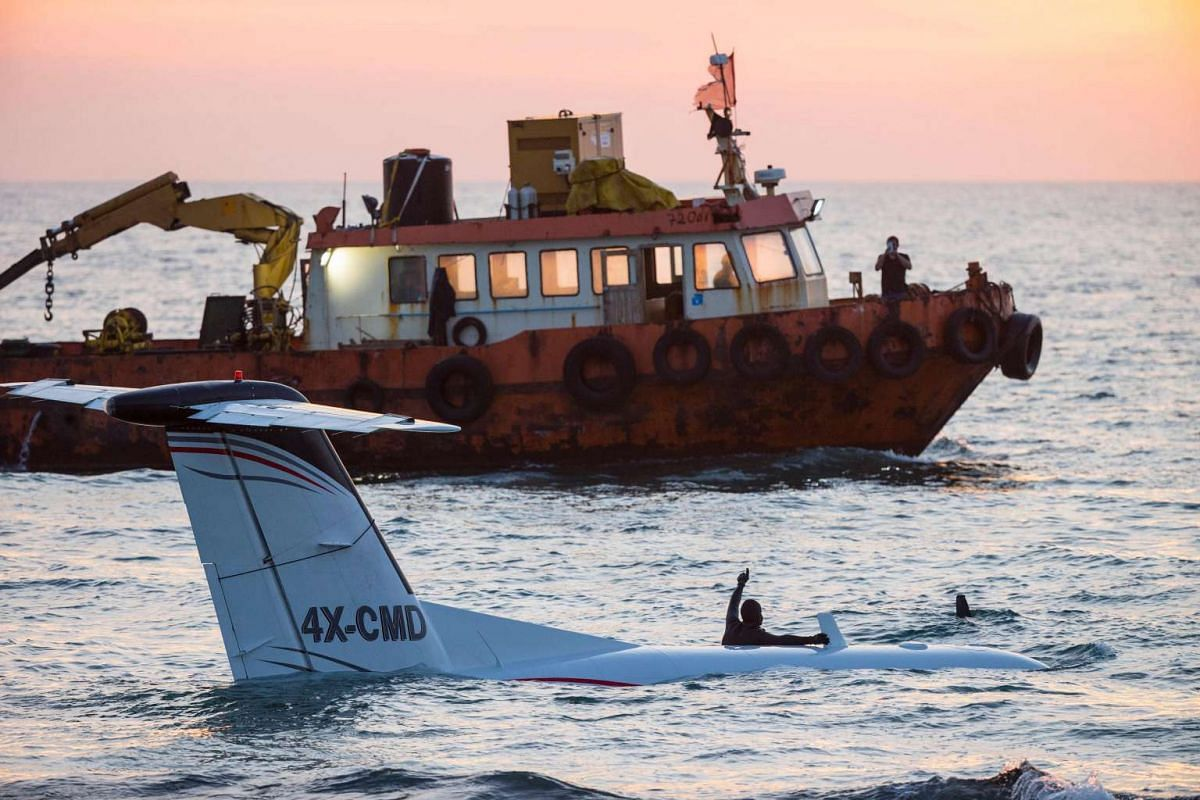 Members of the Israeli rescue team work around a light Israeli aircraft after it made an emergency landing in the Mediterranean sea off the shore of the Israeli city of Tel Aviv, on April 3, 2016. PHOTO: AFP