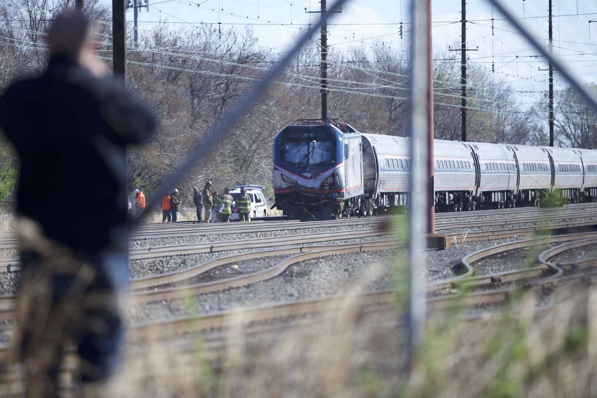 A man observes the crash site of Amtrak Palmetto train 89 on April 3, 2016 in Chester, Pennsylvania. Two people are confirmed dead after the lead engine of the train struck a backhoe that was on the track sourth of Philadelphia, according to publishe