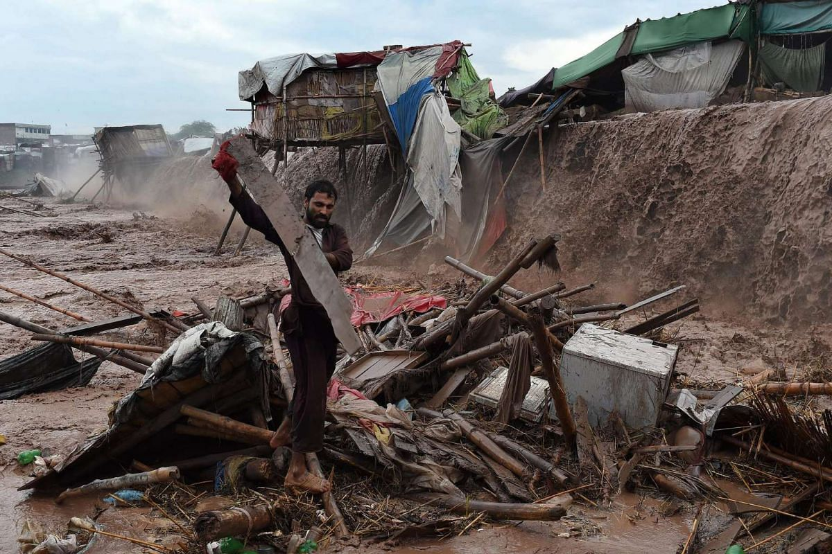 Flood waters rush through a Pakistani market area as a man tries to salvage materials on the outskirts of Peshawar on April 3, 2016.  PHOTO: AFP