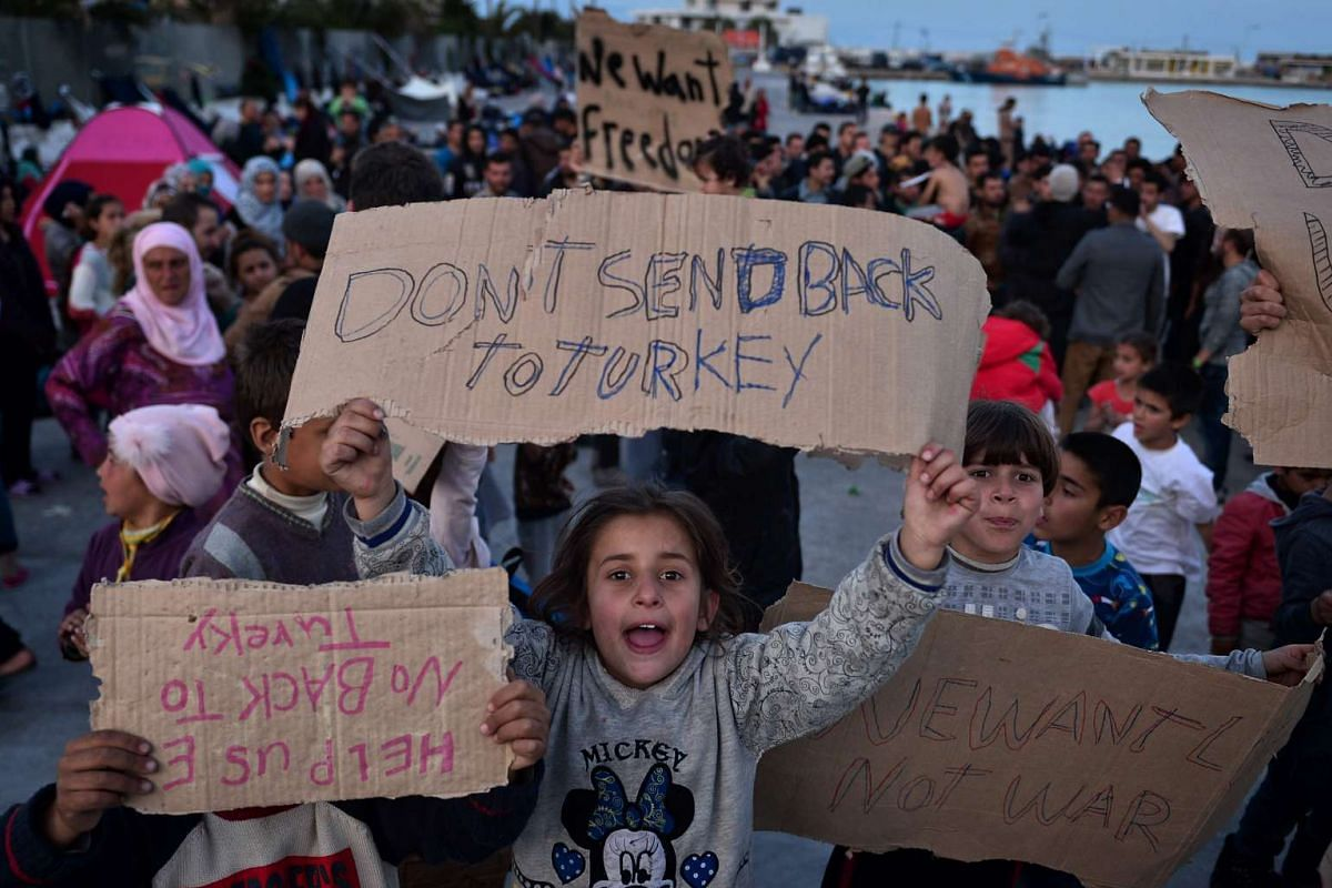 Children hold placards as refugees stage a new protest at the port of Chios where refugees and migrants, who broke out from the Vial detention center, camp out on April 3, 2016. PHOTO: AFP