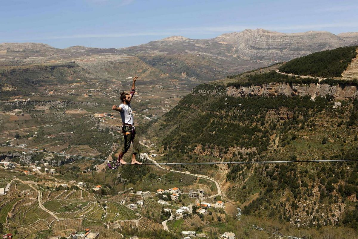 Lebanese Gino Traboulsi walks on a tightrope over the valley of Afqa, northeast of the capital Beirut, on April 3, 2016. PHOTO: AFP