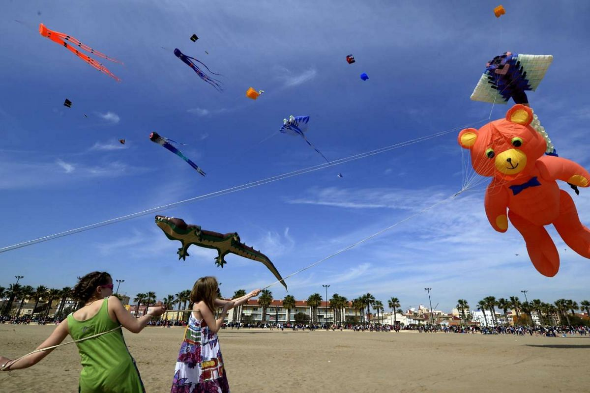 Spectators watch as others fly kites during the international air festival held on Malvarrosa beach in Valencia on April 3, 2016. PHOTO: AFP