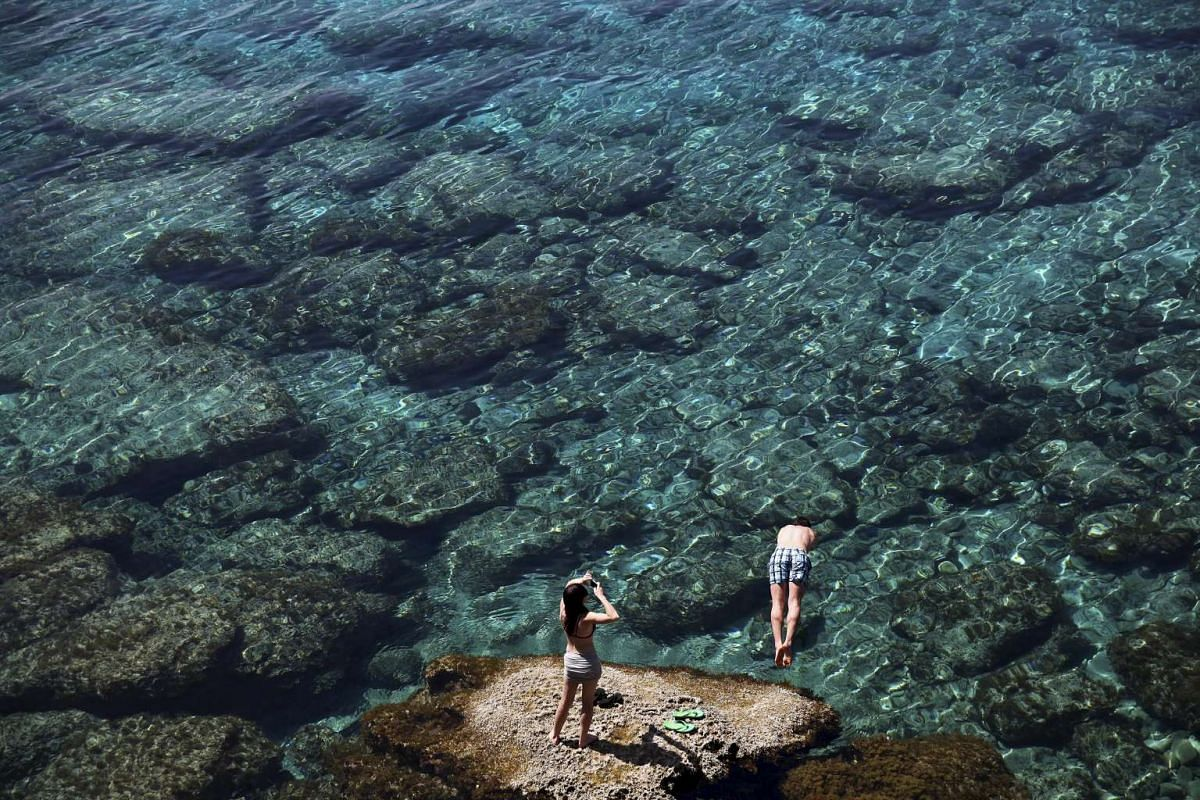 A tourist jumps in the sea as another takes pictures near Cape Greco, Cyprus April 3, 2016. PHOTO: REUTERS