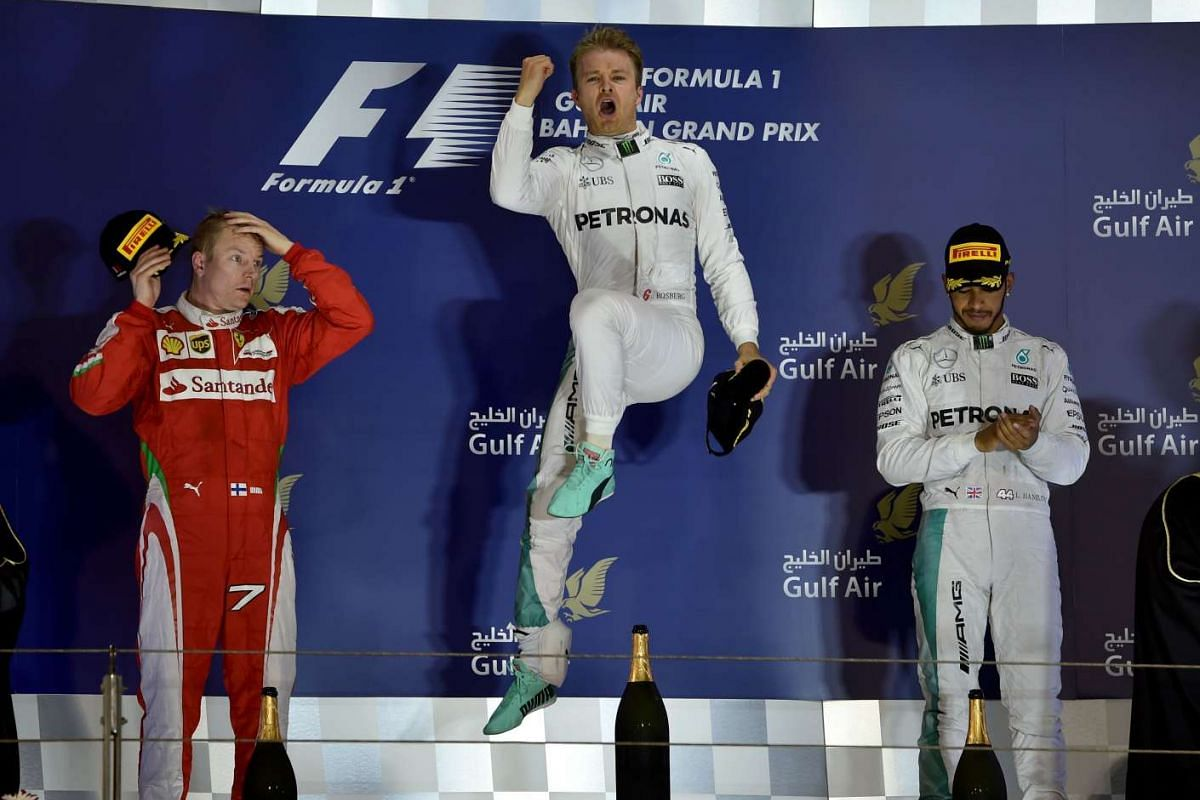 Mercedes AMG Petronas F1 Team's  driver Nico Rosberg (C) celebrates on the podium after winning the Bahrain F1 Grand Prix next to second placed Ferrari's driver Kimi Raikkonen (L) and third placed Mercedes AMG Petronas F1 Team's driver Lewis Hamilton