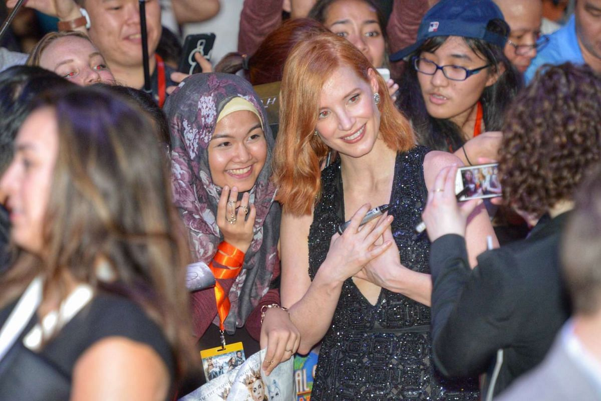 Hollywood star Jessica Chastain taking a photo with a fan on the red carpet for the premiere of fantasy-action movie The Huntsman: Winter's War.