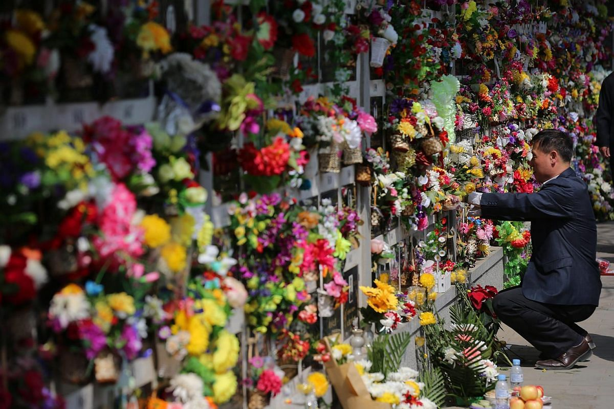 A Chinese man brings flowers to the gravesite of his deceased relatives to mark the Qingming festival in Beijing on April 4, 2016.
