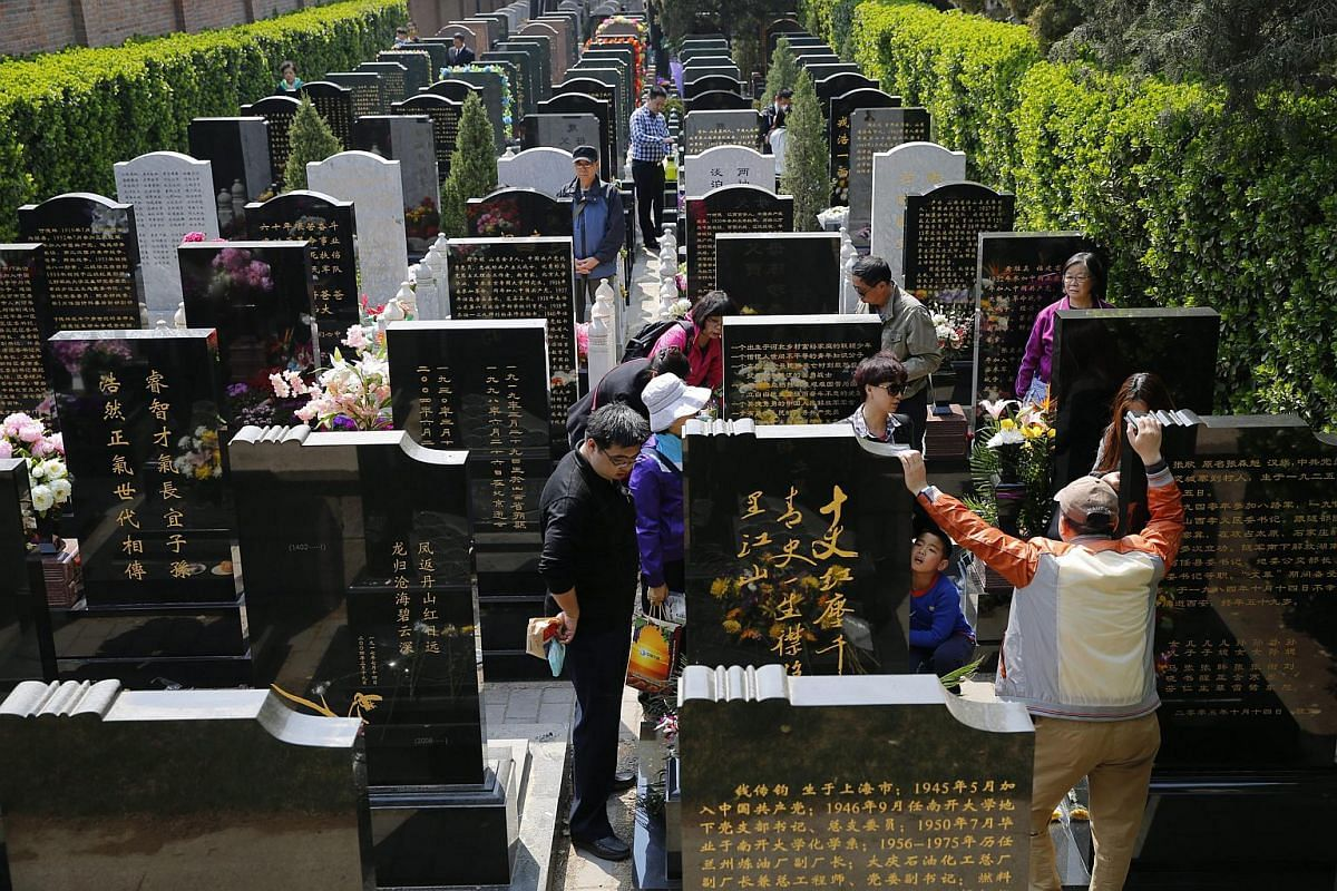 Chinese people stand among gravestones of their deceased relatives to mark the Qingming festival in Beijing on April 4, 2016.
