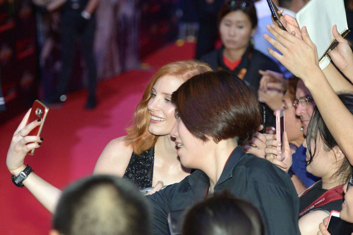 Hollywood star Jessica Chastain taking a selfie with a fan on the red carpet for the premiere of fantasy-action movie The Huntsman: Winter's War.