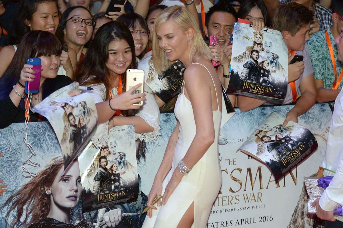 Hollywood star Charlize Theron taking a selfie with a fan on the red carpet for the premiere of fantasy-action movie The Huntsman: Winter's War.