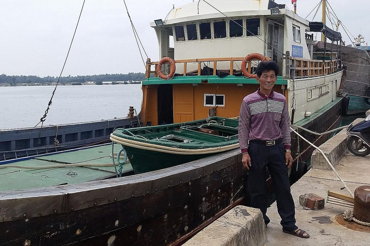 Mr Lin Guanyong (top) was once detained by the Vietnamese authorities while fishing in the Paracels. Fishermen unloading their harvest (above) at Tanmen fishing port in Hainan province. Mr Shi Yingbo has been fishing in the Spratlys for years, follow