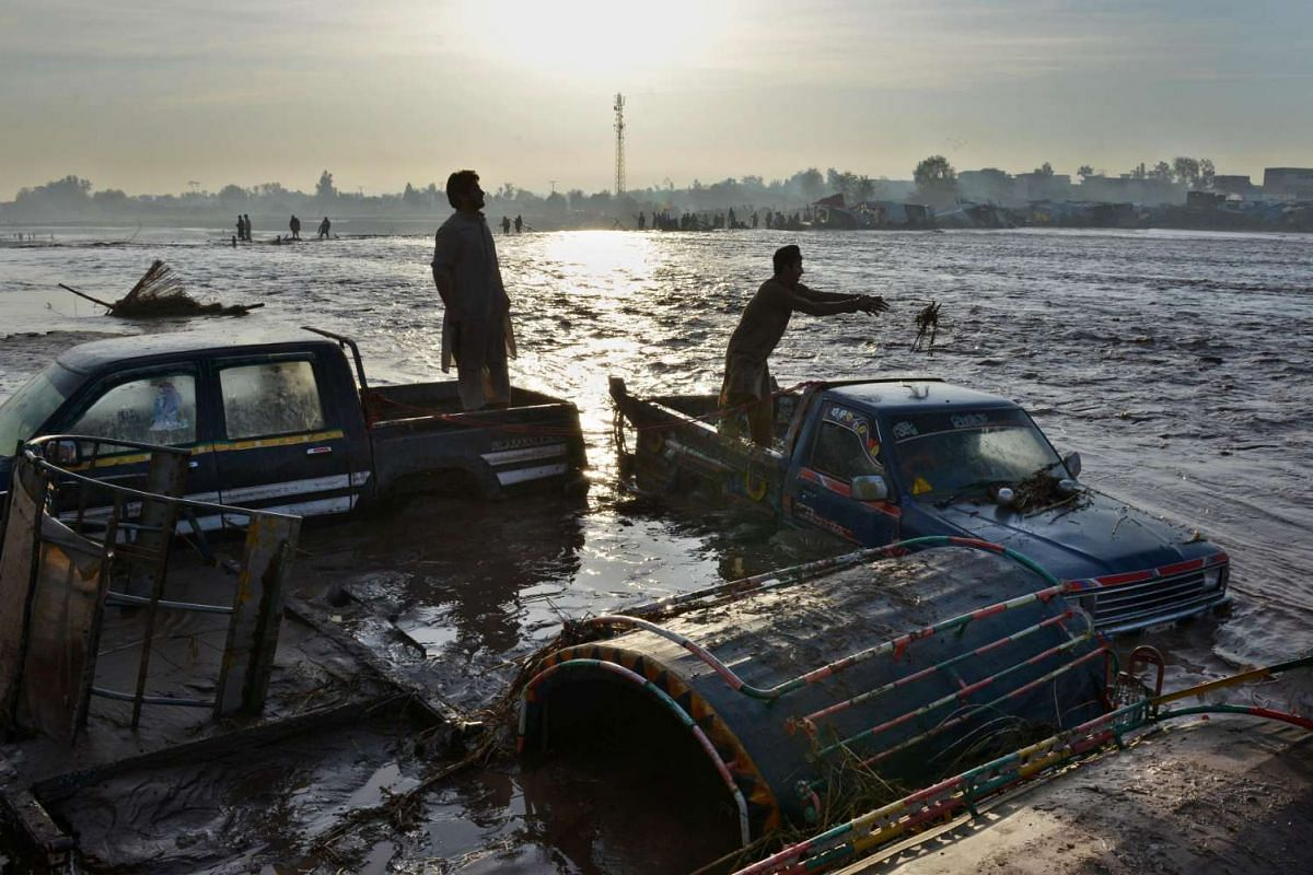 Pakistani men standing on top of their vehicles, submerged by flood waters following heavy rain, on the outskirts of Peshawar on April 4, 2016.