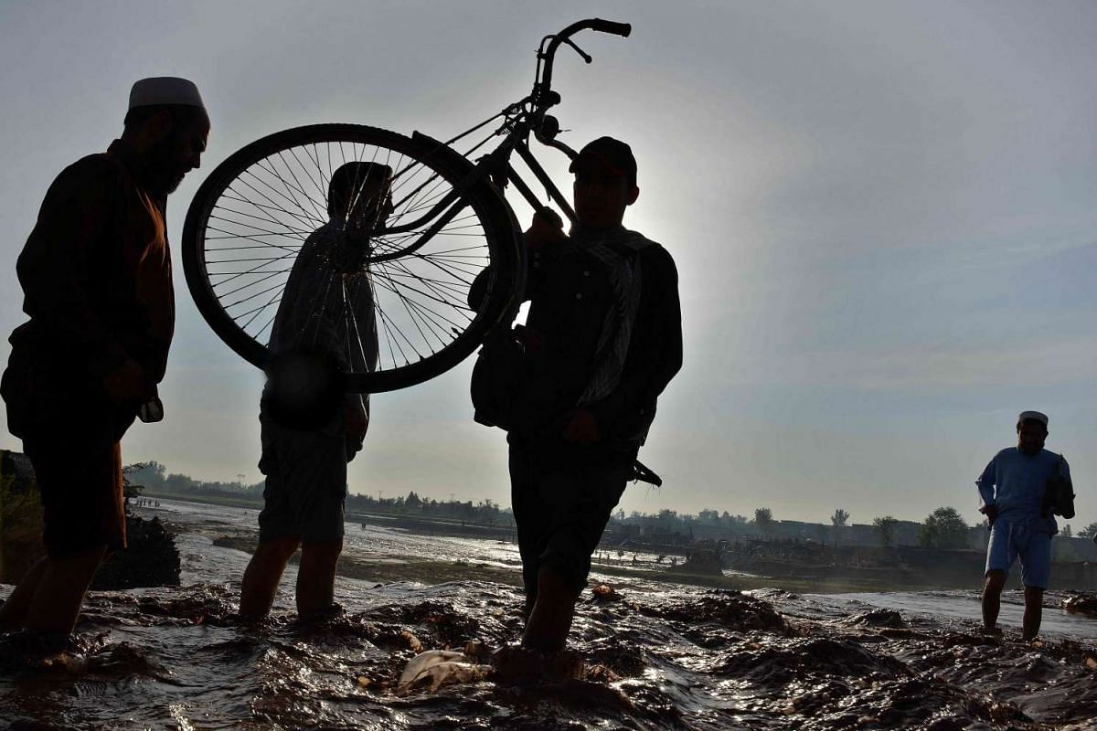 A Pakistani resident carrying his bike across a flooded street, following heavy rain on the outskirts of Peshawar, on April 4, 2016.