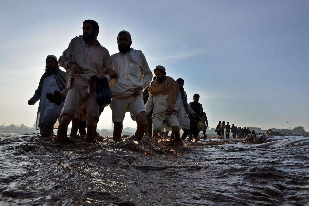 Pakistani residents crossing a flooded street following heavy rain on the outskirts of Peshawar on April 4, 2016.