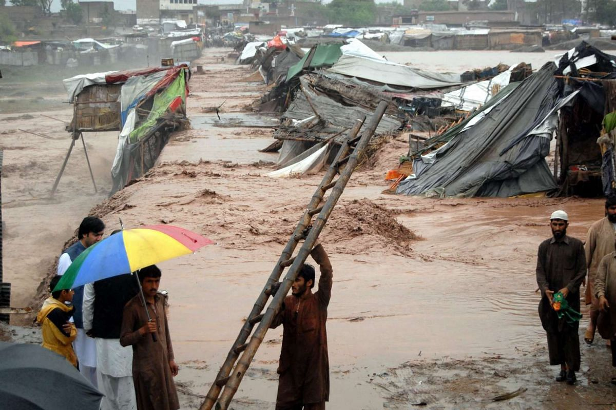 People gathering around their shops after they were swept away by flash floods triggered by heavy rainfall, on the outskirts of Peshawar, Khyber-Pakhtunkhwa province, Pakistan, on April 3, 2016.