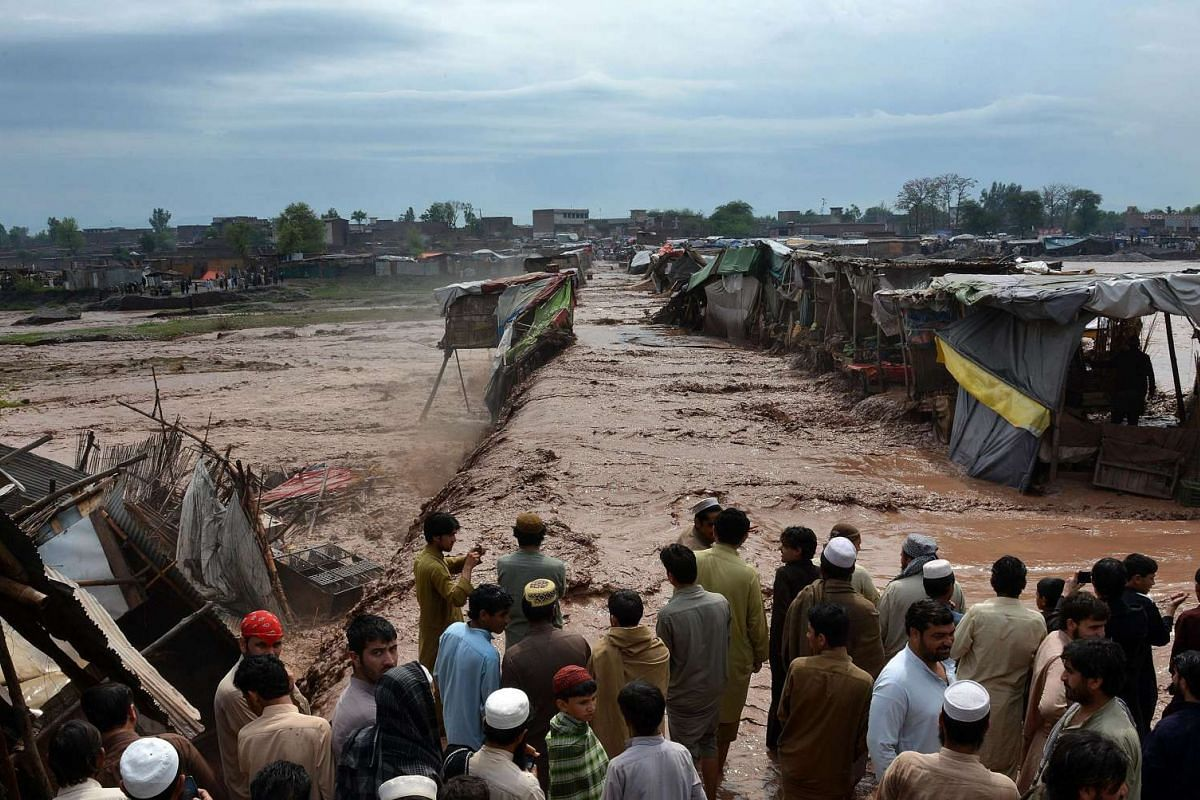 Pakistani vendors and residents gathering beside flood waters rushing through a market area on the outskirts of Peshawar on April 3, 2016.