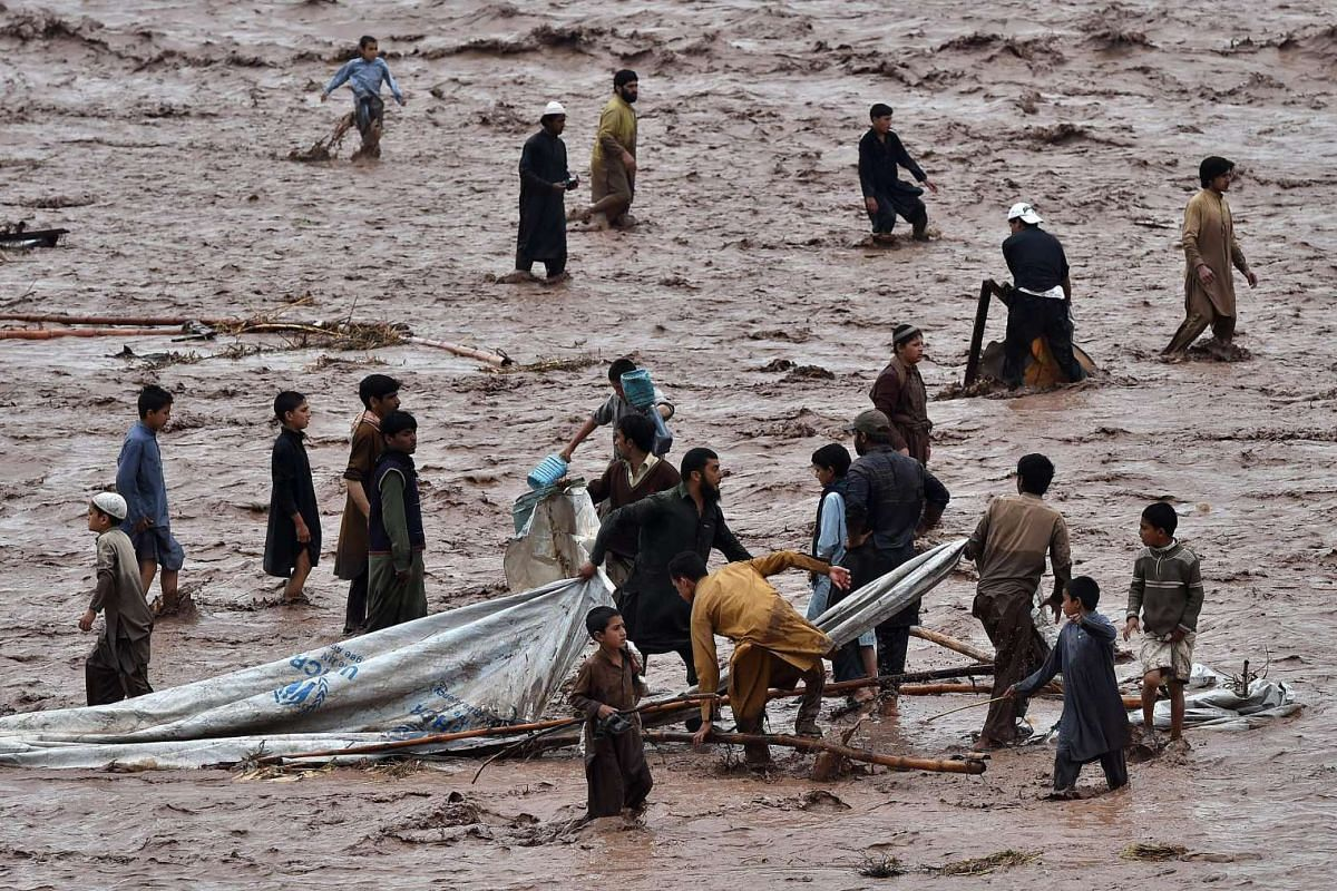 Vendors and resident scrambling to save their possessions as flood waters rush through a Pakistani market area, on the outskirts of Peshawar on April 3, 2016.