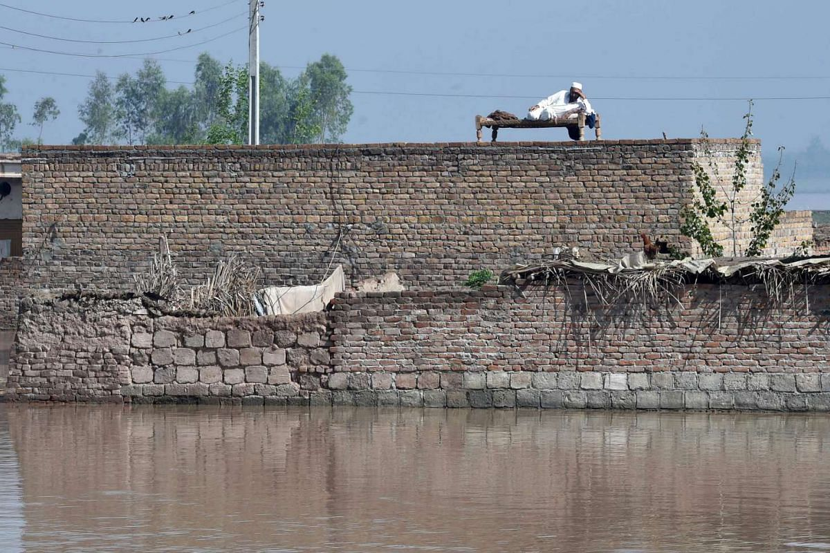 A Pakistani resident resting on top of his house at a flooded area on the outskirts of Peshawar, following heavy rain, on April 4, 2016.