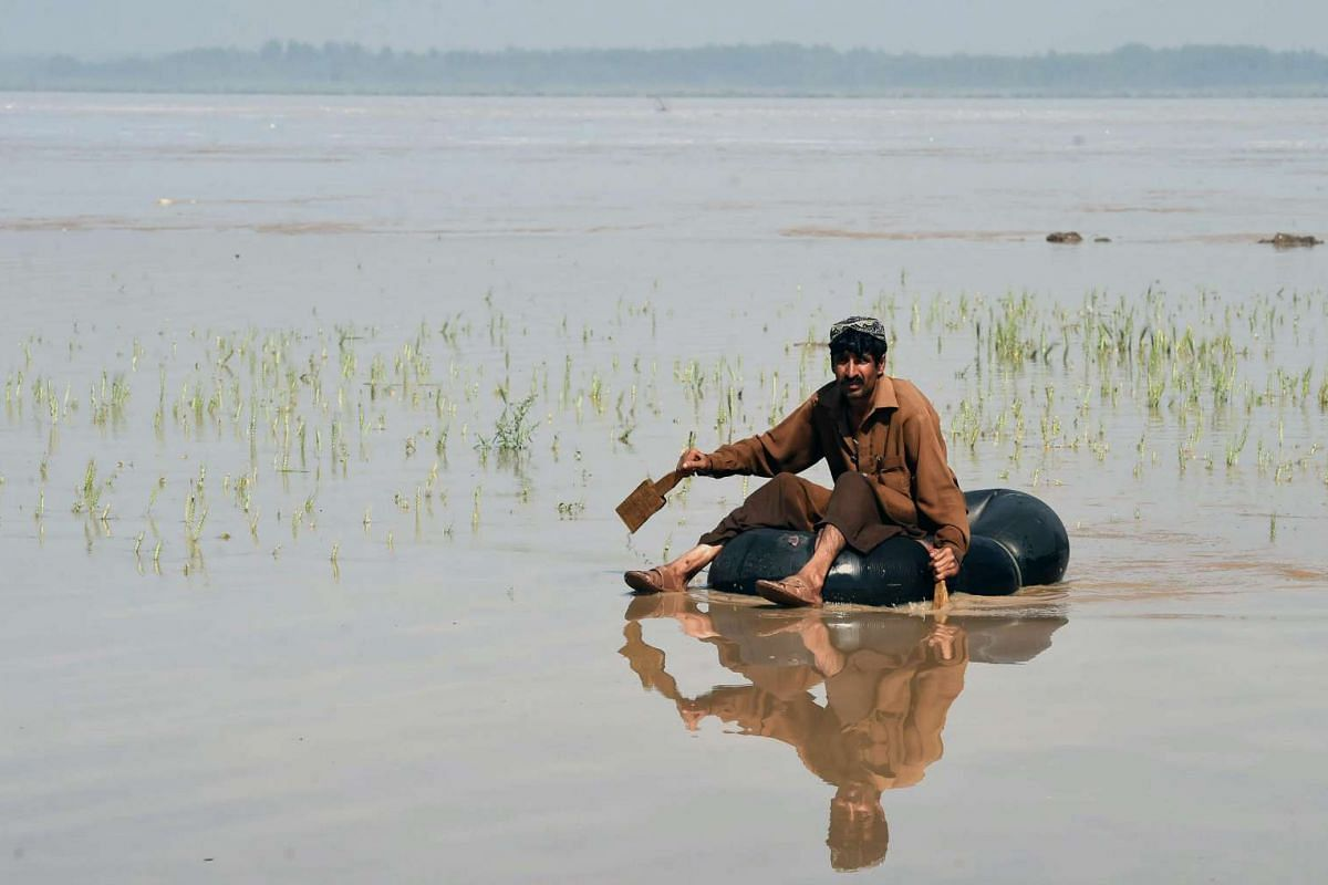 A Pakistani resident sitting on an inner tube in a flooded area on the outskirts of Peshawar, following heavy rain, on April 4, 2016.
